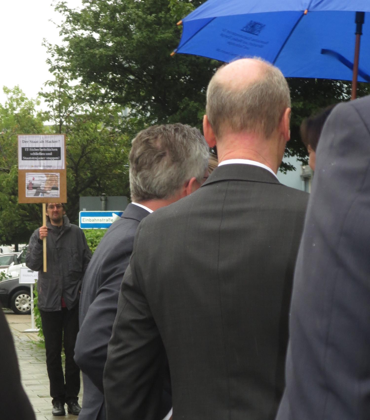 Im Vordergrund: Überwachungsminister de Maizière, im Hintergrund vermiest ein Kritiker den Wahlkampfauftritt.